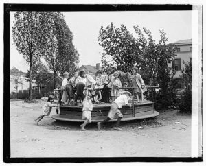 Children on a small go-round in a playground sometime around 1920.