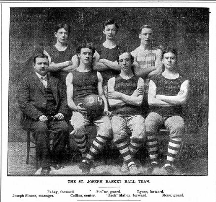 Six basketball players in striped socks seated with their coach.