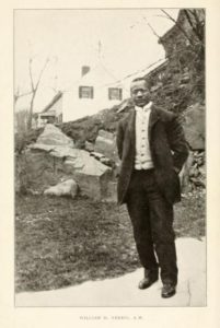 Photo of William H. Ferris standing in rocky New England landscape.