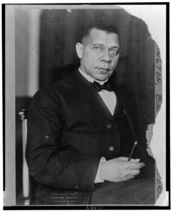 Seated  three-quarter lenth portrait of Booker T. Washington with a writing implement in his right hand.