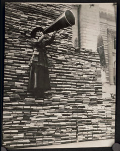 Image of librarian with megaphone in front of a wall of books donated for soldiers in WWI.