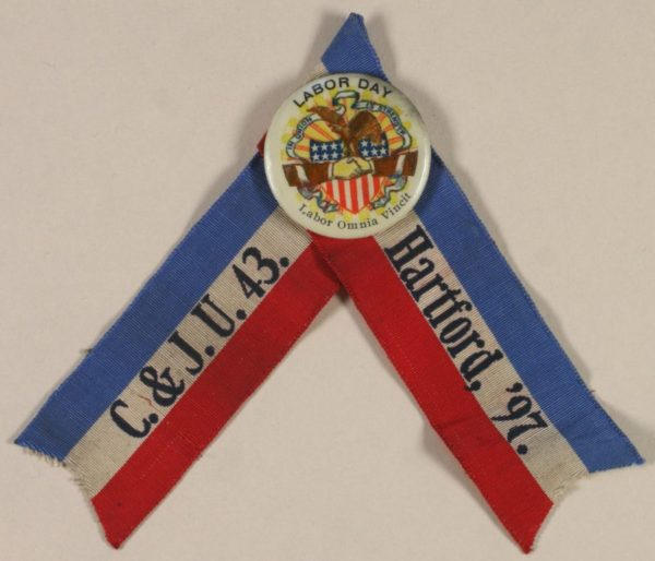 "Image of a red, white and blue ribbon in an upside down ""v"" shape with a badge and pin for the Carpenters and Joiners Union, Local 43. It is dated 1897."