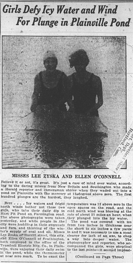 Image of two young women standing waist-deep in frigid water.