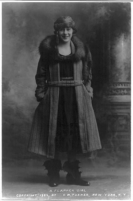 Photo of a young flapper dressed in a wool coat with a fur collar, a cloche hat with a tassel, and rubber galoshes with the clamps left open.